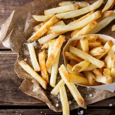 Fast food french fries potatoes with skin served with salt and herbs in lunch box on baking paper over old dark wooden background. Top view, space for text